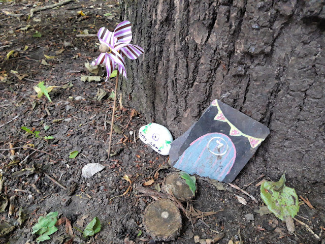 A small blue fairy door against a tree trunk.  There is a stripy windmill and a painted pebble next to the door.