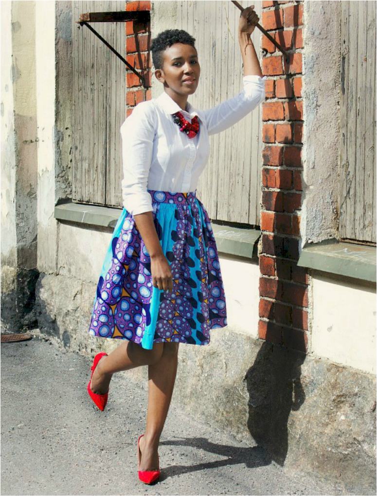 woman holding to hook on a wall is wearing white shirt, african print skirt, and red pumps.