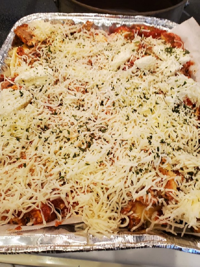 this is a large pan of quick lasagna with lots of noodles cheese and meats in it