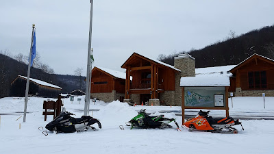 Snow mobiles parked in front of Pennsylvania Lumber Museum