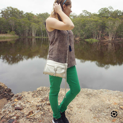 awayfromblue Instagram | green skinny jeans and animal print tank with sneakers at lake spring outfit