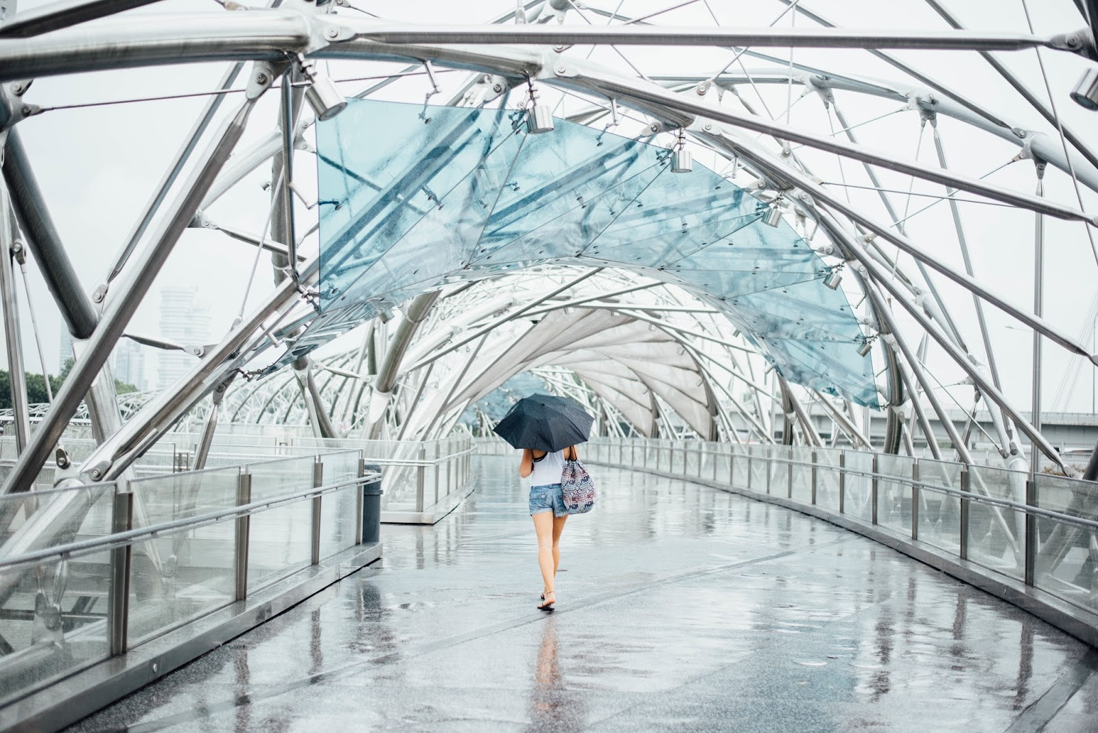 Blue Monday surival tips - woman with an umbrella walking along a walkway