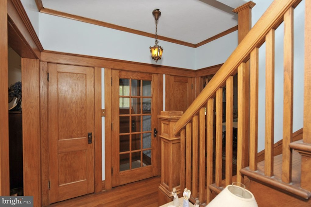 color, interior photo of entry hall, looking out to vestibule and two closets in front of house