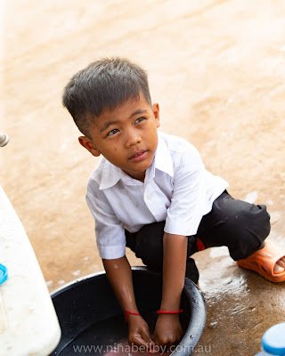 Young Cambodian Kindergarten boy washing his lunch dishes in a bowl of water on the ground before he can play