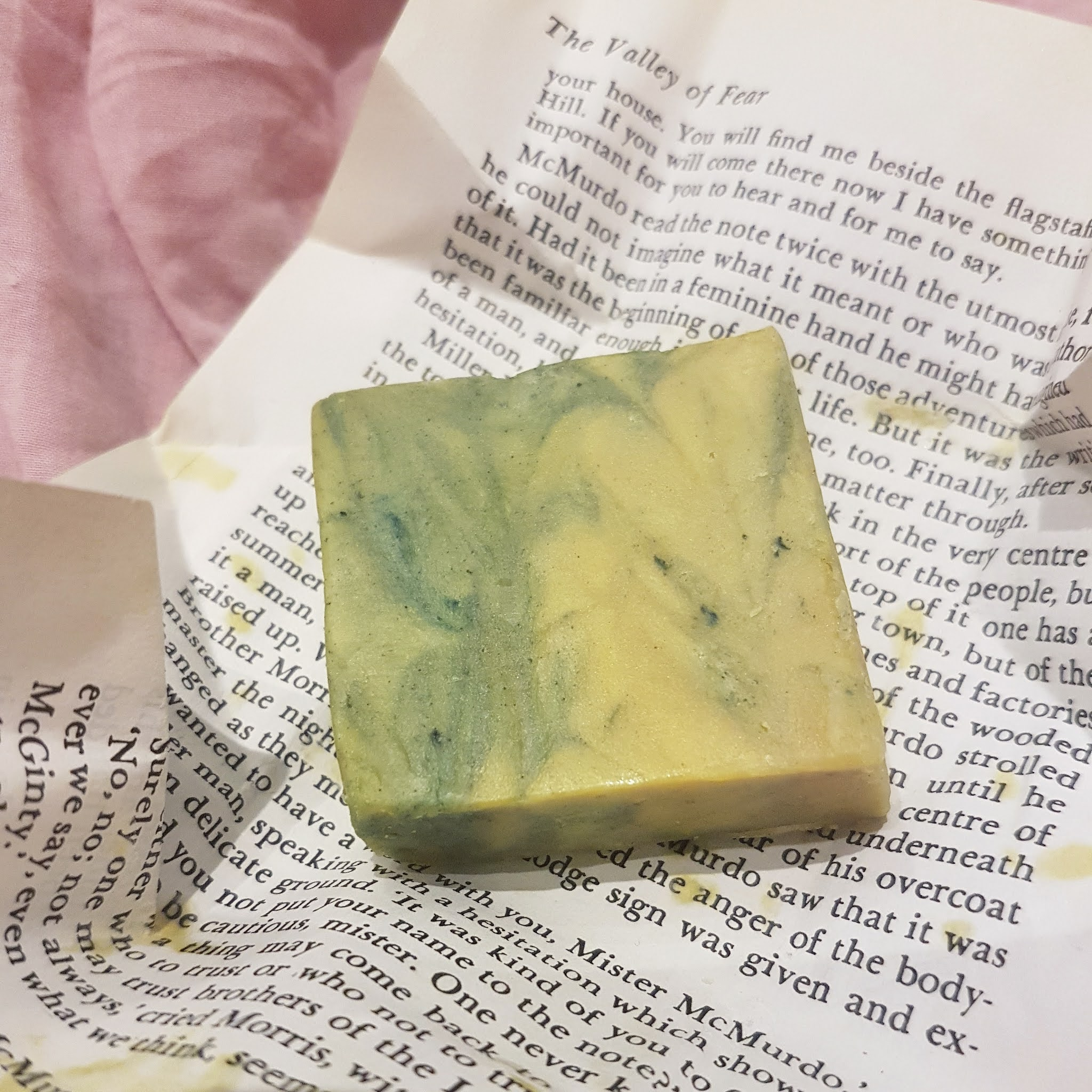 deep yellow shampoo bar from Natural Wisdom with blue green ripples throughout , lying on top of an old book page