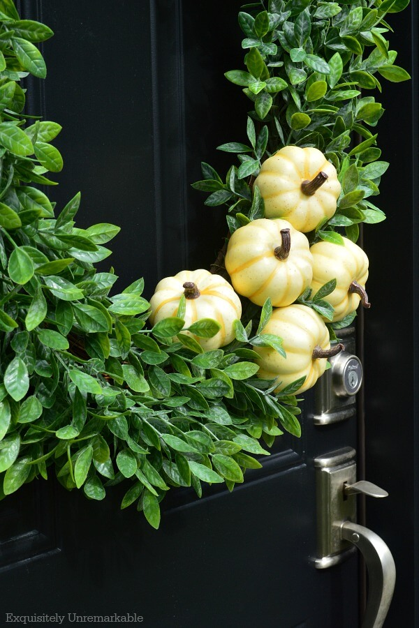 Simple Fall Boxwood Wreath With White Pumpkin On A Black Door