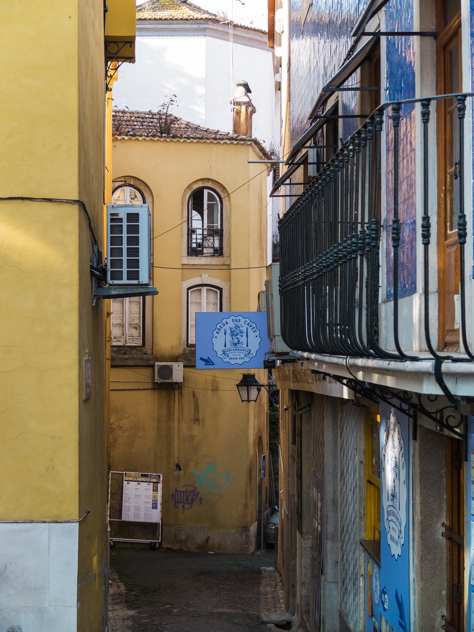 View of yellow buildings and a black railing in an alley in Sintra, Portugal.
