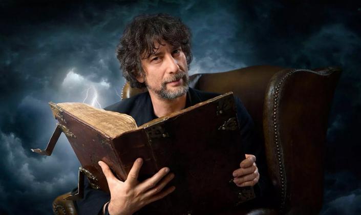 Imagem de capa: o autor Neil Gaiman, um homem branco de cabelos pretos longos e bagunçados, barba e em um terno preto, com um livro antigo com capa marrom na mãos, sentado em uma poltrona velha e marrom, e no fundo, um céu de tempestade com raios cortando o ar.