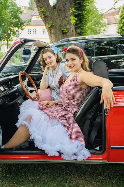 Dancing Lilly und Elli vom UTSC dancefire in kleidern von boutique new vintage in einem roten oldtimer sitzend bei rocknroll im kurpark Bad Sauerbrunn