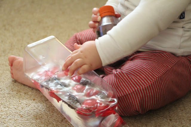 Baby playing with a discovery bottle with water, rose petals and lavendar