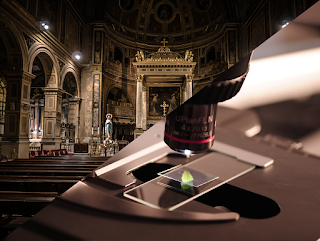 Image is divided on the diagonal. In the upper left is a view of the interior of a heavily-ornamented cathedral, while in the lower right is an image of a microscope examining a slide with a piece of leaf.