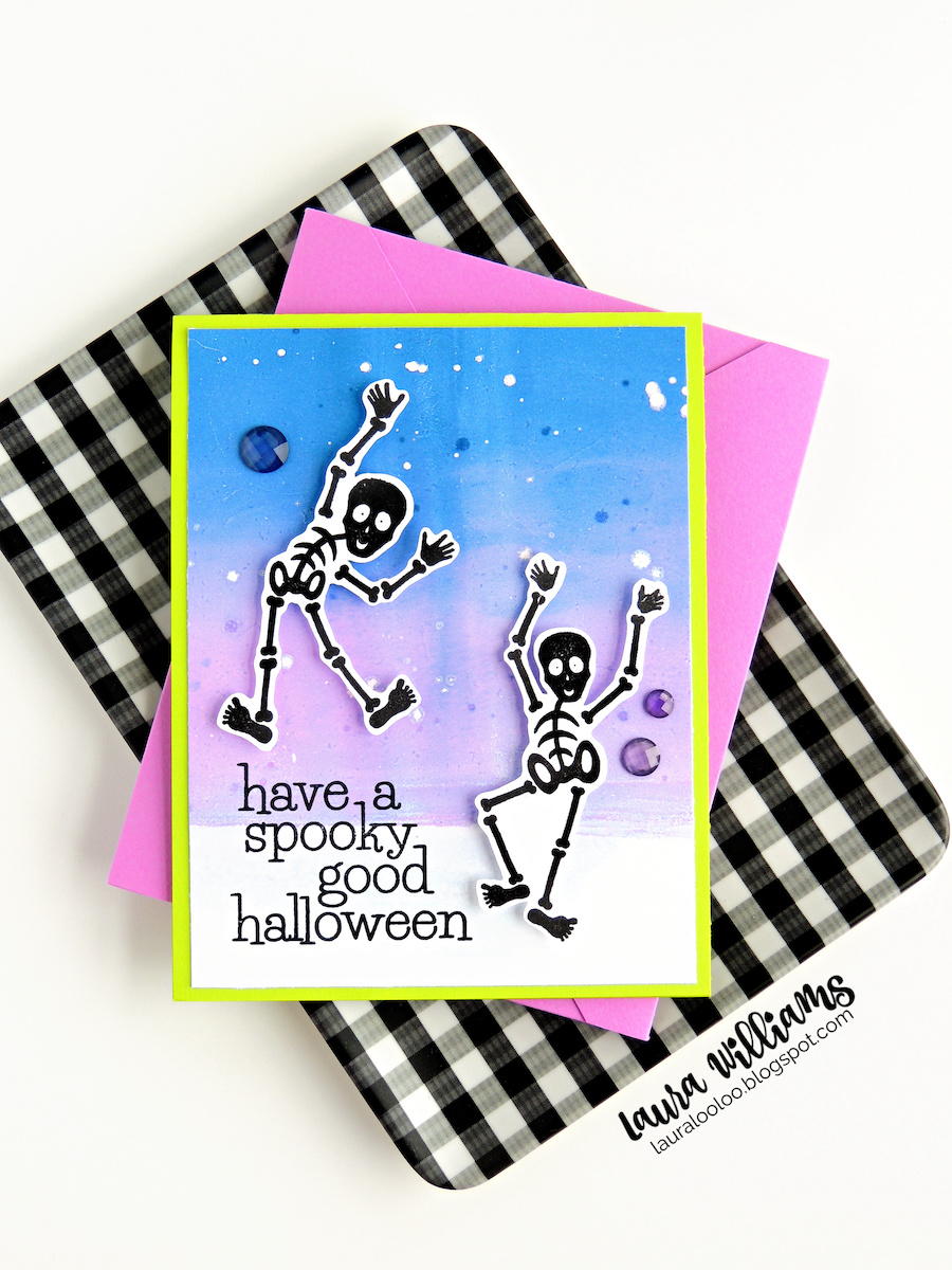 """A sweet and spooky handmade Halloween card with two rubber stamped skeletons, embossed in black, trimmed and attached to a blue and purple blended background, created on the Gel Press. The card is on a lime green card base and has the sentiment """"Have a spooky good Halloween"""". In this photo, the card is resting with a purple envelope, on a black and white gingham tray. All of the stamps are from Impression Obsession."""