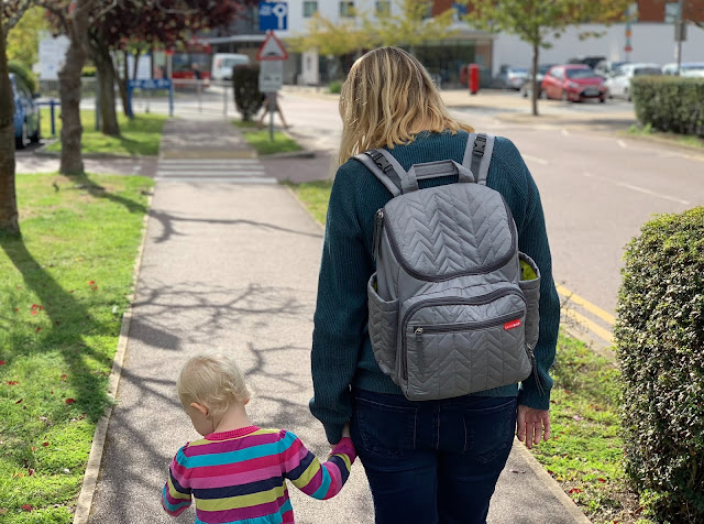 A mum wearing a grey backpack holding a toddlers hand while walking along