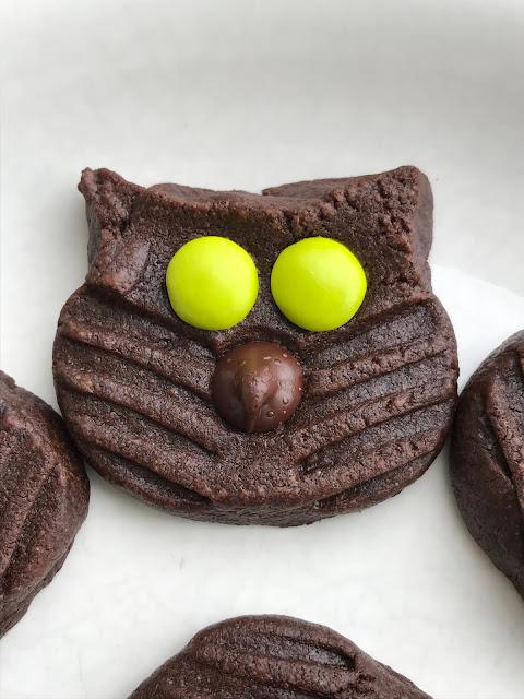 Close-up of a dark chocolate black cat cookie.