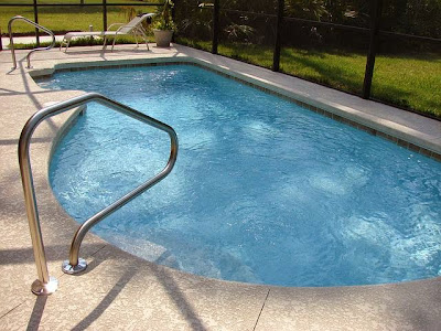 Picture of a kidney shape swimming pool viewed from the entrance ladder. This article is about 12 steps on how to build a swimming pool.