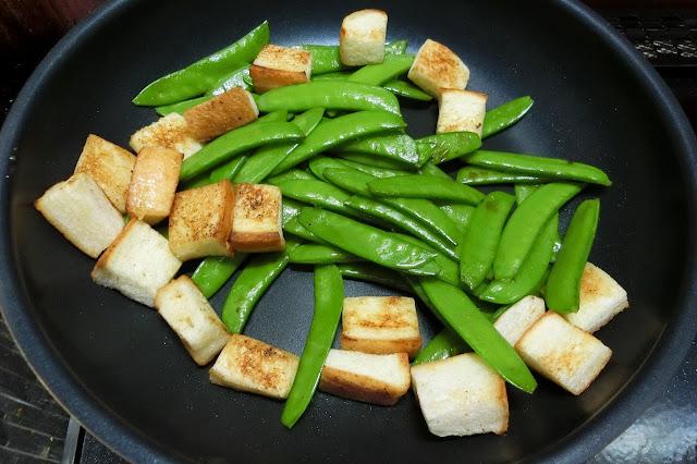 同じフライパンにさやえんどう、食パンを入れ、食パンの表面にこんがり焼き色がつくまで炒め合わせます。 油分が足りなければバターを追加してください。(分量外) 焼けたら一旦両方ボウルに取り出します。