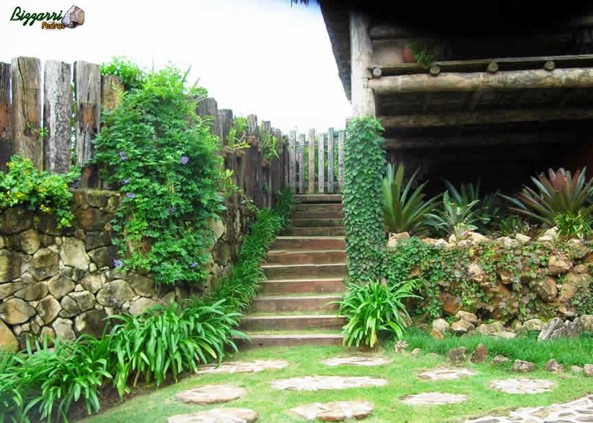 Caminhos de pedra rústica junto ao muro de pedra com a escada de dormentes de madeira.