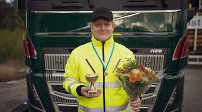 Edwin Hansson med blommor och pokal framför lastbil.