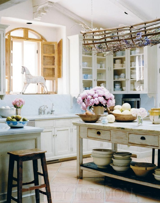 This dreamy kitchen is so homey, it's almost a fantasy - I love the wooden cabinets and stacked dishes under the island