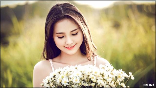 ảnh cô gái ngắm hoa và mỉm cười