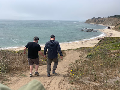 Leo and his dad, seen from behind, walking down a trail to a cove.