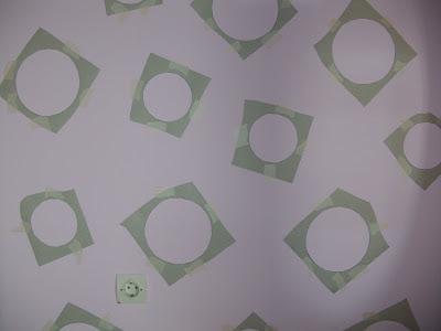 Στερεώνουμε τους κύκλους από χαρτόνι στον τοίχο με χαρτοταινία