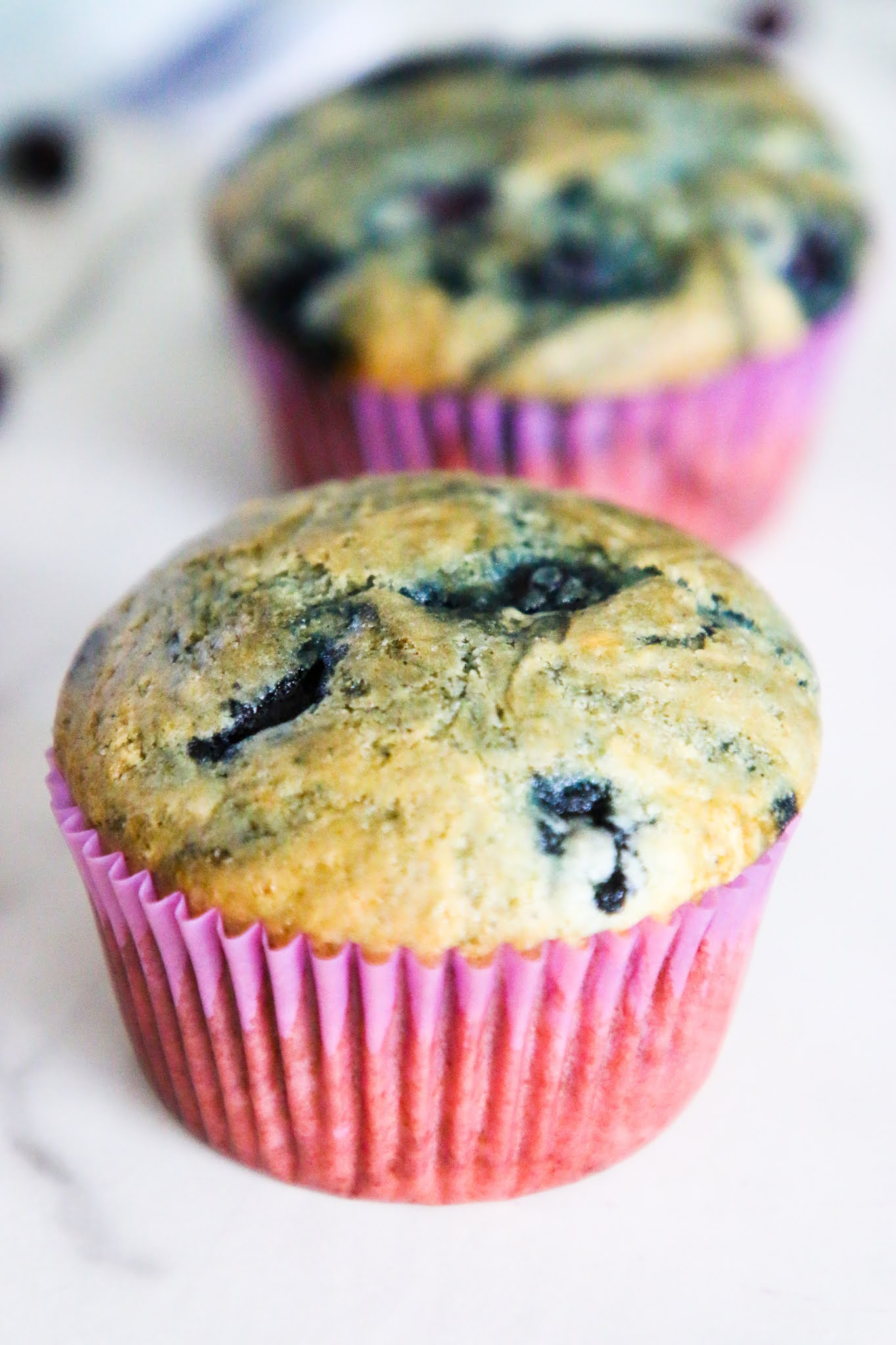 A blueberry muffin on a marble table with another muffin in the background