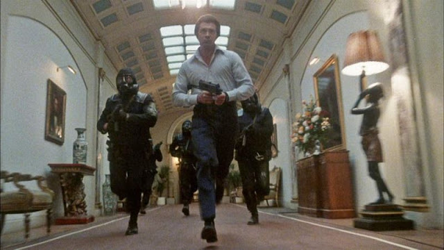 Lewis Collins and SAS men running along a corridor