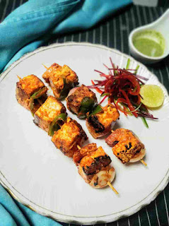 Paneer tikka serving in a garnished plate, green chutney in background