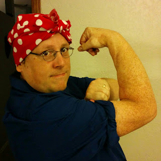 The author, in his Halloween costume as Rosie the Riveter, wearing the dark blue shirt and red bandana with white dots, striking the traditional 'We Can Do It!' pose with one arm flexed as the other arm rolls up the shirt sleeve.