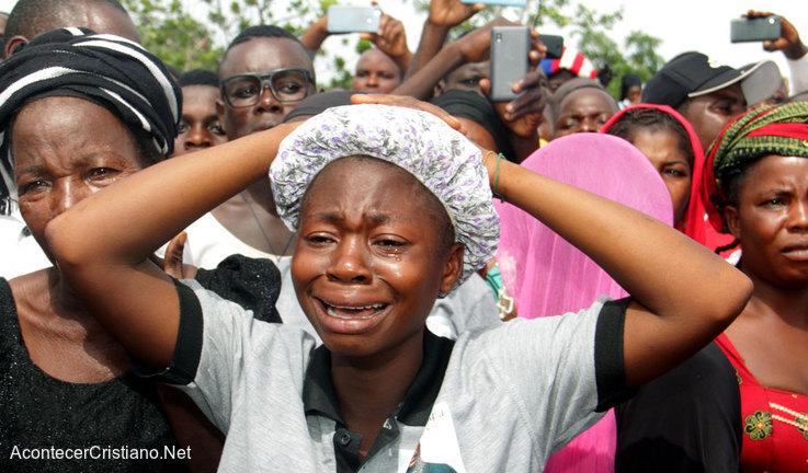 Familiares de cristianos lloran en funeral