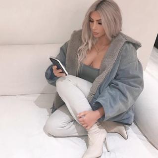 Kim Kardashian sitting pressing phone