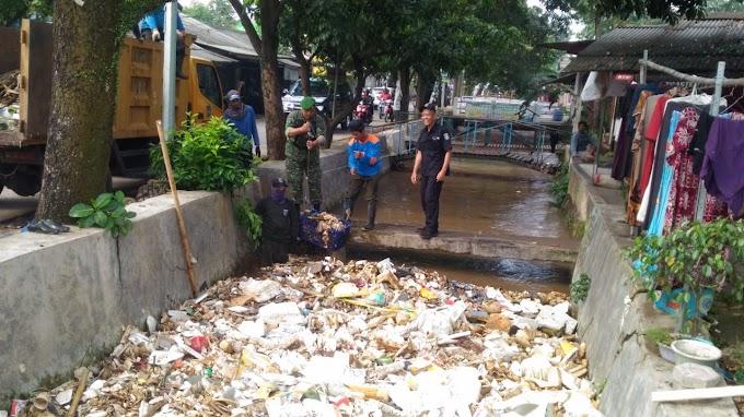 Aksi Babinsa Koramil 07/Limo Bersihkan Tumpukan Sampah di Irigasi