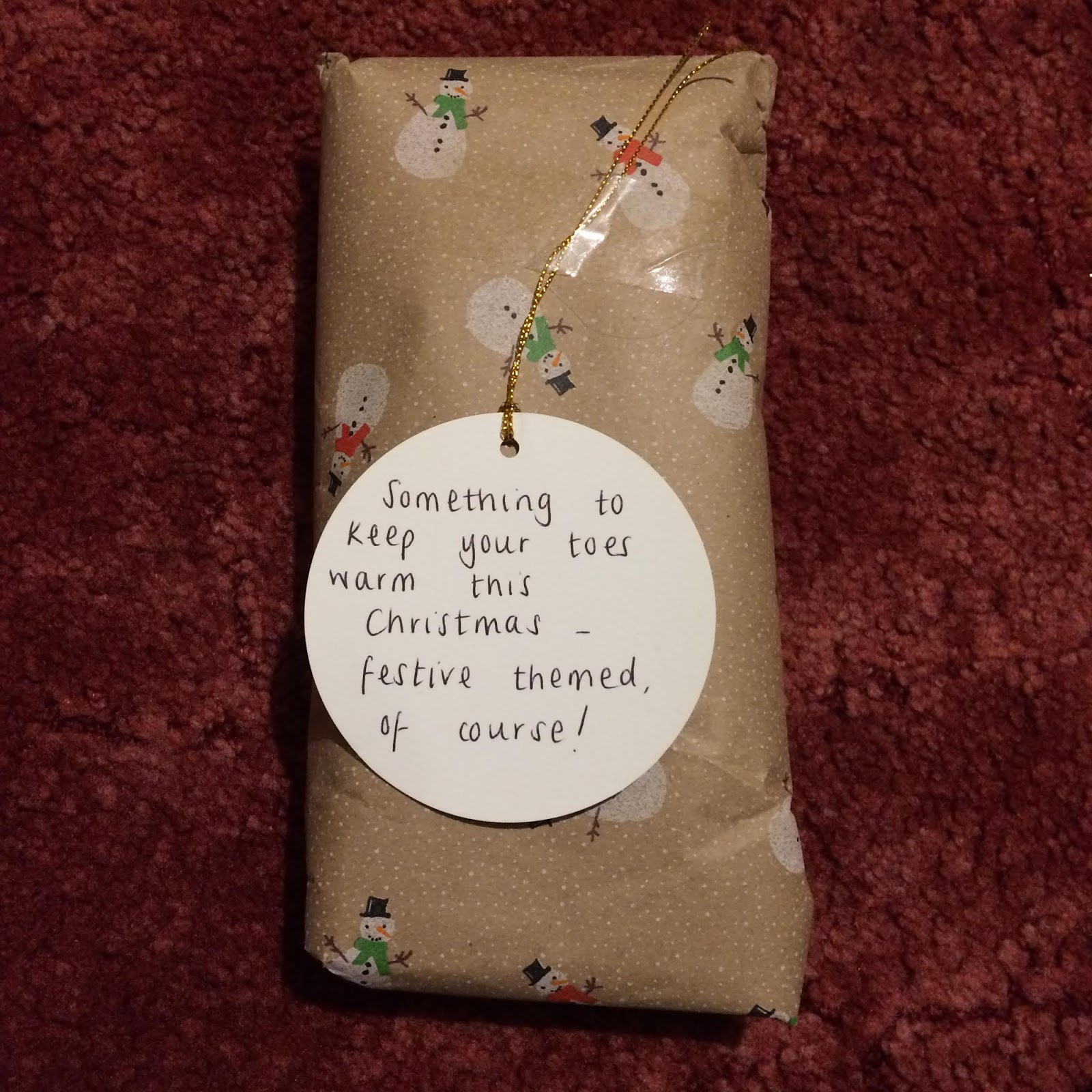A wrapped present with a tag reading, Something to keep your toes warm this Christmas - festive themed, of course!