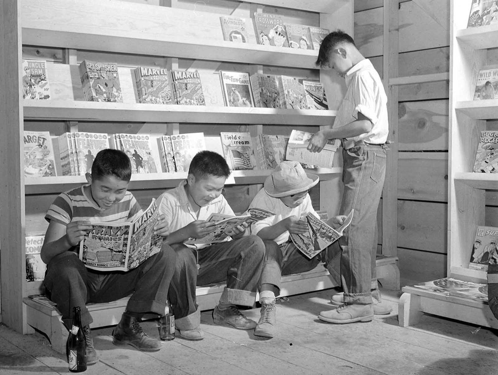 Four young evacuees from Sacramento, California, read comic books at the newsstand in the Tule Lake Relocation Center, in Newell, California, on July 1, 1942.