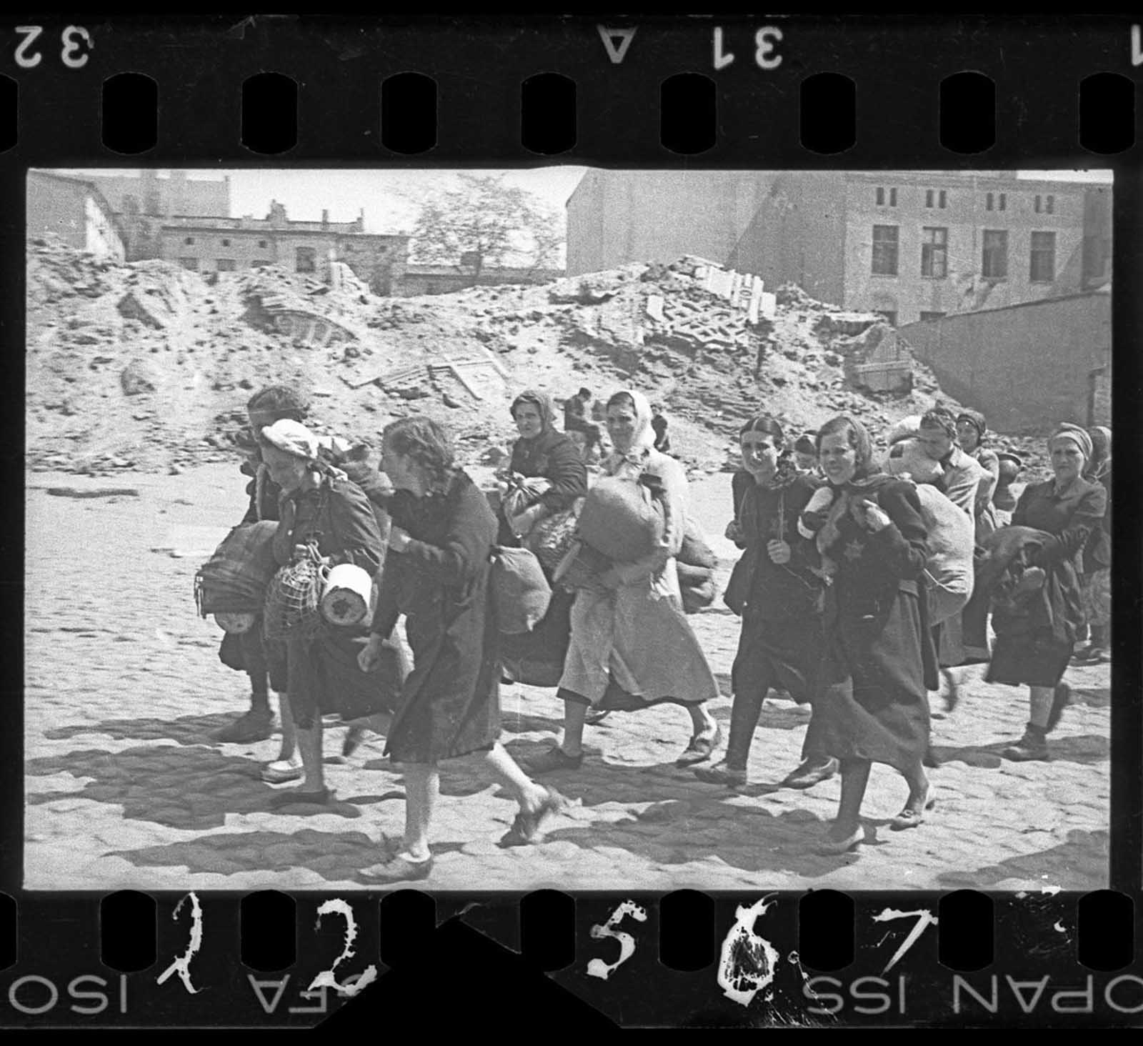 A group of women with sacks and pails, walking past synagogue ruins heading for deportation.