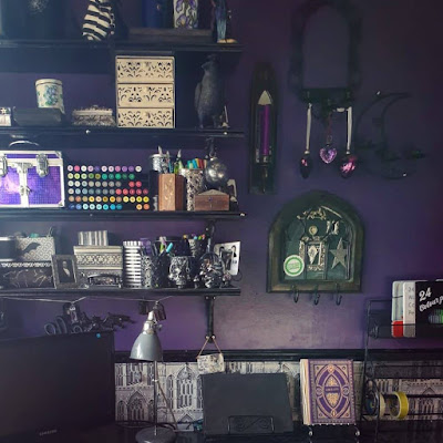 Black shelves with ornate (but difficult to see) brackets upon which are art materials; skull tub with purple and green dragon-scale paint brushes, vintage tins, ivory drawers, a purple box with silver strapping and latches. Next to the shelves are a variety of Gothic arch candle holders. On the left is a tall, slim dark brown one with gold trim and a mirror, it is also a sconce for a purple dinner-style candle. Central at the top is a black metal arch with some swirls and three candle holders, but the candle-holders are being used to suspend three purple glass hearts. Bottom centre is a dark brown wooden Gothic arch, short and squat, with three metal wire Gothic arches inside it, a mirror and a Highlands & Islands Scottish Green Party sticker. On the right is a crescent moon mirror of black metal, also with three candle-holders. The wall they are on is dark purple. To the right there is a black metal shelf with trays of pencils and charcoals. The computer monitor is on the left. In the middle of the desk are a grey vintage-style desk-lamp, a computer tablet in a black metal recipe book holder, and what looks like a gold and purple antique book but is actually a Harry Potter book lamp. The desk is black marble effect. Behind the monitor, lamps, tablet and bottom of the metal shelves is greyscale Gothic architecture patterned wallpaper under a black dado rail. You are very patient listening to this description, thank-you.