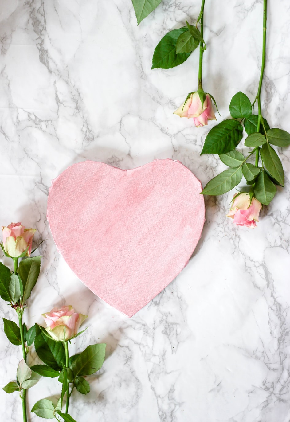 Stock image from unsplash of a pink heart on a marble background