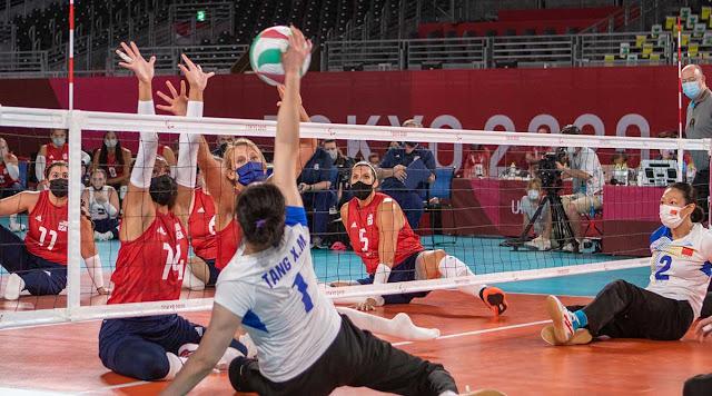 jogadora da China ataca bola no vôlei sentado, com jogadora dos EUA de braços levantados para bloquear