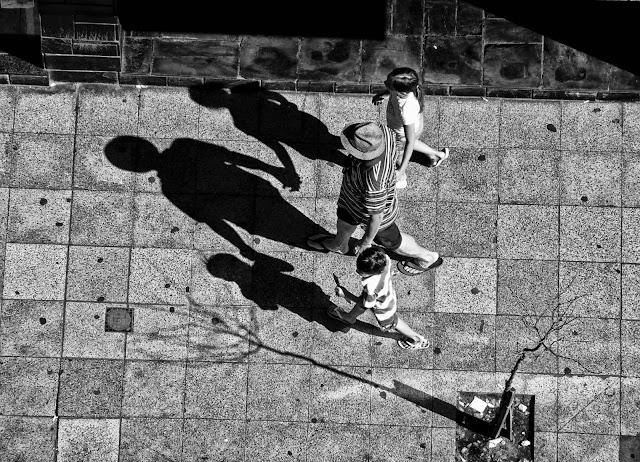 Cenital sobre tres personas caminando detrás de sus sombras.
