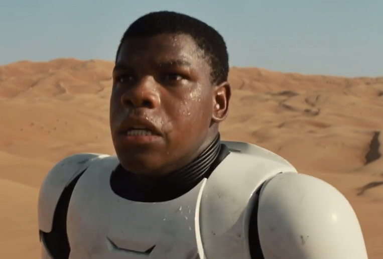 John Boyega's character wearing a stormtrooper uniform looking confused and afraid in the desert