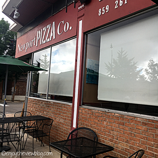 outside Newport Pizza Company - brick building with large windows,a sign above with the name, and wrought iron tables and chairs outside