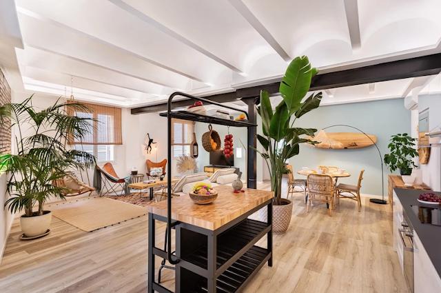 Salón abierto a la cocina con decoración de inspiración tropical.