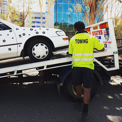 White car with black daisies on it being mounted onto a tow truck.