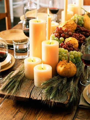 These candles, fresh fruit and mini pumpkins on a piece of wood are great rustic fall decor options.