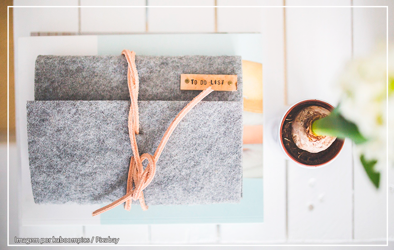 A imagem mostra um diário cinza fechado com uma tira de couro sobre uma mesa branca; Ao lado do diário está um pequeno vaso de planta, com uma plantinha crescendo