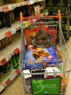 boy in shopping trolley, camouflaged