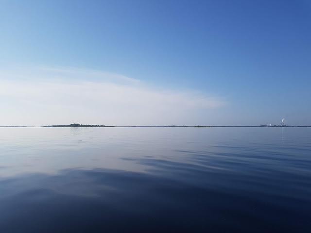 Tyyneltä mereltä katsottuna horisontissa siintää saari ja Kemin Ajoksen tehtaat