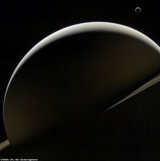 This image shows Saturn splendor with some parts illuminated by the Sun, while the dust ring also can be seen surrounding the planet. Titan can also be seen at the top right of Saturn. Faint greenish tint to the left of Saturn is the rest of the camera glare that can not be removed