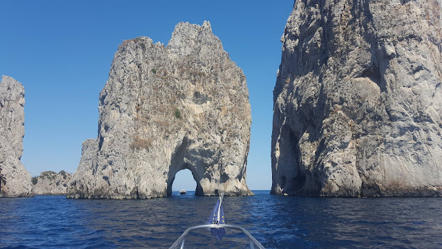 Huge grey rock formations stick out of the blue sea. The centre shows a boat passing through a natural archway in one of the formations.